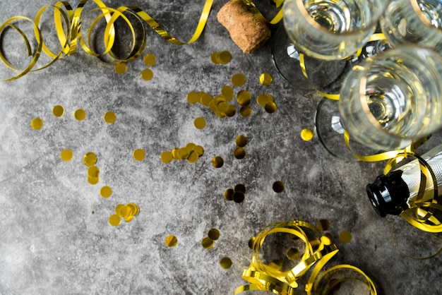 Elevated view of golden confetti and streamers with empty glass over concrete textured