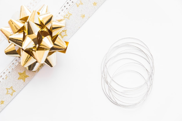 Elevated view of golden satin ribbon and silver string on white background
