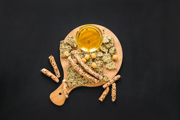 Elevated view of granola bar with oil on wooden chopping board against black background