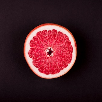 An elevated view of grapefruit cross-section against black background
