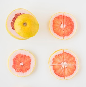 An elevated view of grapefruit cut in different slices on white backdrop