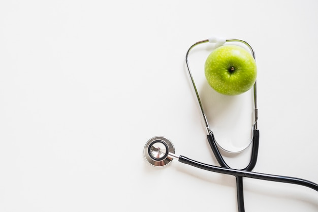 Elevated view of green apple with stethoscope on white background
