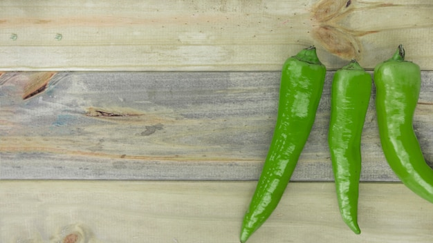 Elevated view of green chili peppers on wooden backdrop