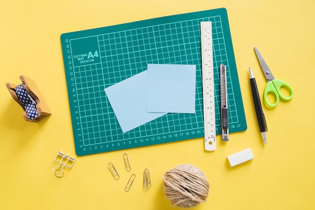 Elevated view of green cutting mat and stationeries on yellow background