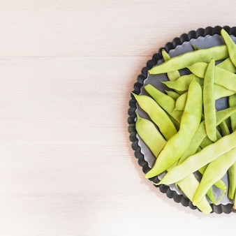 Elevated view of green hyacinth beans on baking tray over wooden backdrop