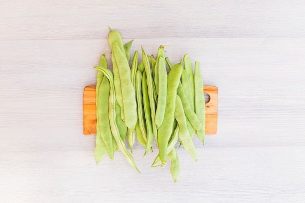 Elevated view of green hyacinth beans on wooden cutting board