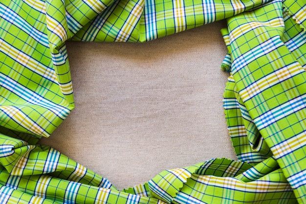 Elevated view of green plaid pattern textile forming frame