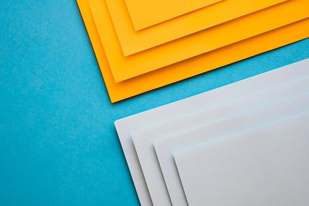 Vista elevata delle carte di cartone grigio e giallo sulla superficie blu