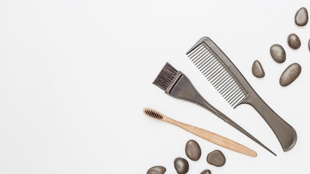 Elevated view of haircomb; pebbles and brush on white backdrop