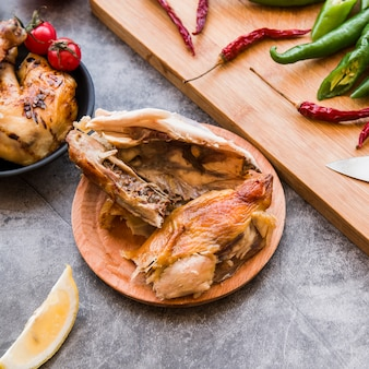 Elevated view of half eaten roasted chicken with red and green chilies
