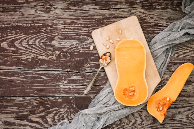 An elevated view of halved butternut squash with seeds on chopping board over the wooden desk