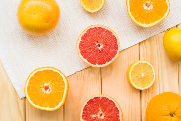Elevated view of halved citrus fruits on wooden background