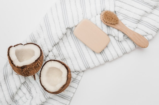 Elevated view of halved coconut; towel; soap and brush on white backdrop
