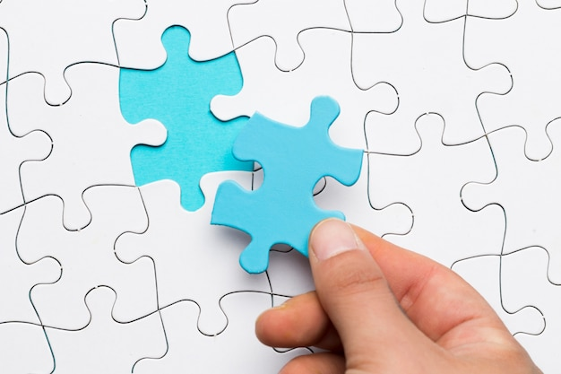 Elevated view of hand holding blue puzzle piece over white puzzle background
