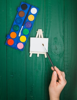 Elevated view of hand holding paint brush over mini easel and watercolor palette