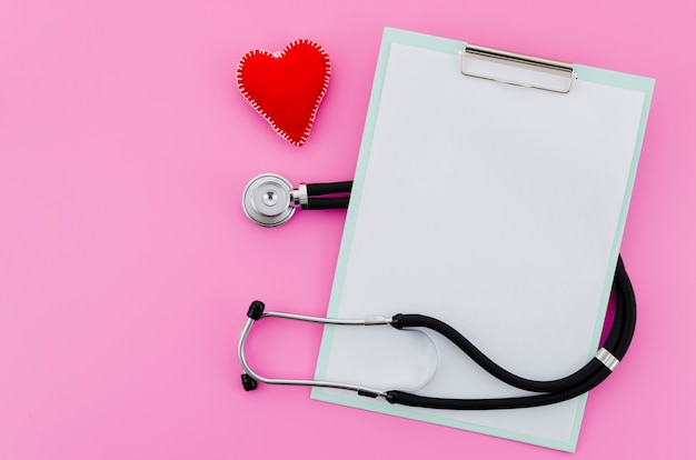 An elevated view of hand-made red heart with stethoscope and clipboard on pink background