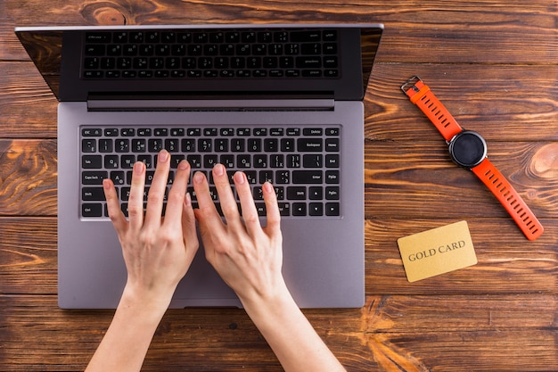 Elevated view of hand typing on laptop over wooden table