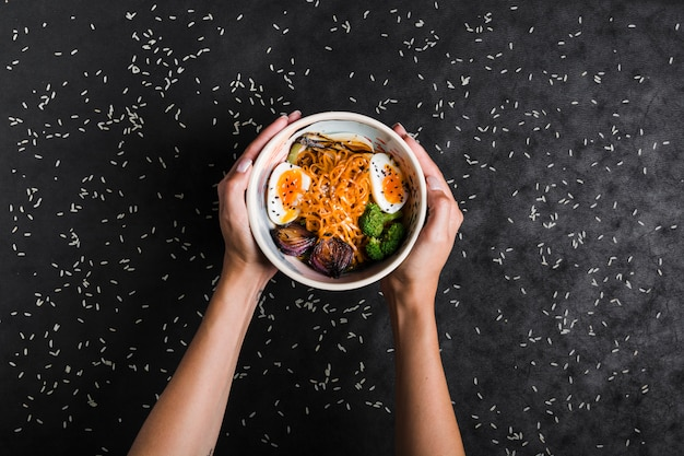 An elevated view of hands holding bowls of ramen noodles with eggs and salad spread with rice grains on black background