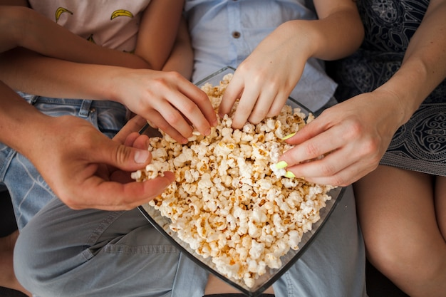 Elevated view of hands holding popcorn at home
