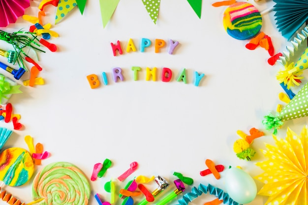 Elevated view of happy birthday text with party accessories on white surface