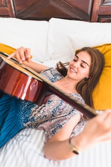 Elevated view of happy teenage girl lying on bed playing guitar