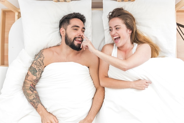 Elevated view of happy woman touching her boyfriend's nose on bed