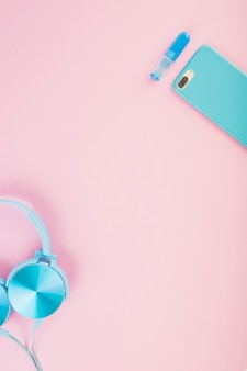 Elevated view of headphone and smartphone on pink background