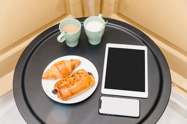 Elevated view of healthy breakfast with electronic gadgets on table