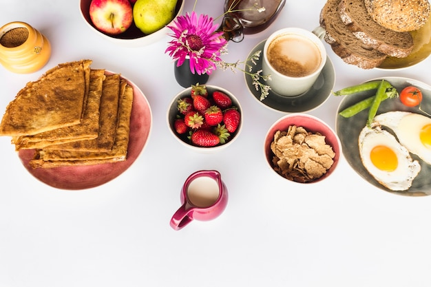 Elevated view of healthy breakfast with fruits on white backdrop