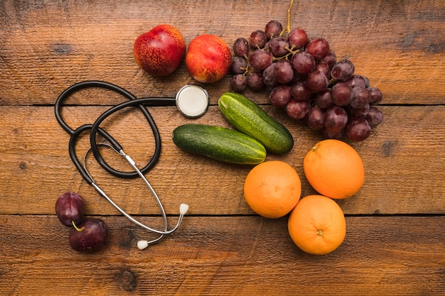 Elevated view of healthy fruits with stethoscope on wooden background