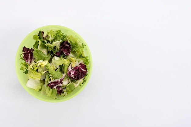 Elevated view of healthy salad in bowl on white background