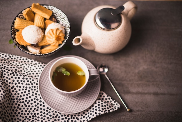 Elevated view of herbal tea; cookies and teapot on table