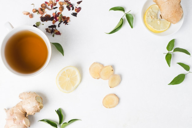An elevated view of herbal tea cup with lemon; ginger and dried herbs on white backdrop