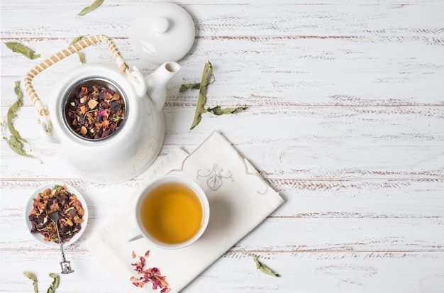 An elevated view of herbal tea and dried herbs on white wooden desk