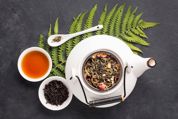 Elevated view of herbal tea and healthy ingredient with fern leaf on black slate background