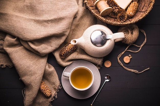 Elevated view of herbal tea; pinecone; teapot; sack; button; wicker basket and ball of yarn on table