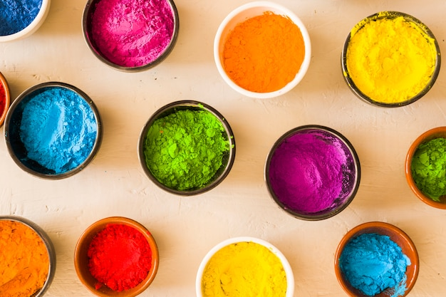 An elevated view of holi color powder in the different type of bowls on concrete backdrop