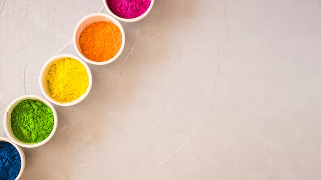 An elevated view of holi color powder in the white bowls on concrete background
