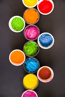 An elevated view of holi powder in the bowls on black background