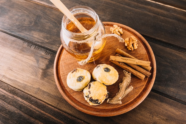 Elevated view of honey; walnut; cinnamon; cup cakes and ginger on wooden board