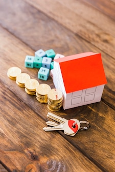 Elevated view of house model, key, math blocks and stacked coins on wooden background