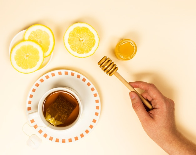 Elevated view of human hand holding honey dipper near healthy tea and lemon slice