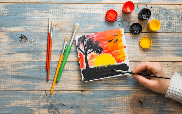 Elevated view of human hand painting sunset seen with paint brush on wooden desk