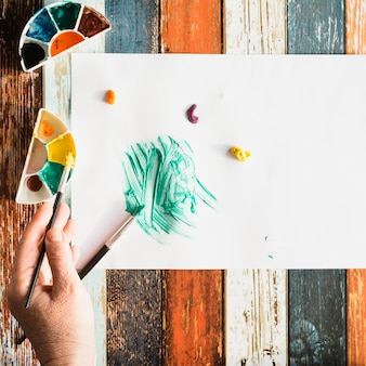 Elevated view of human hand painting on white sheet on grunge wooden background