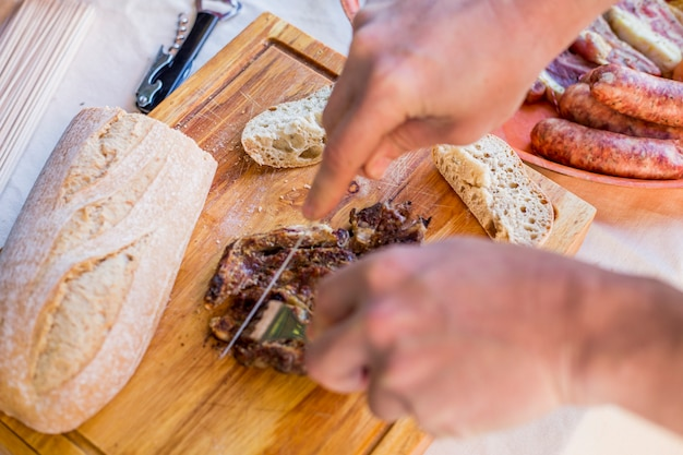 Elevated view of a human hand slicing cooked meat on wooden chopping board