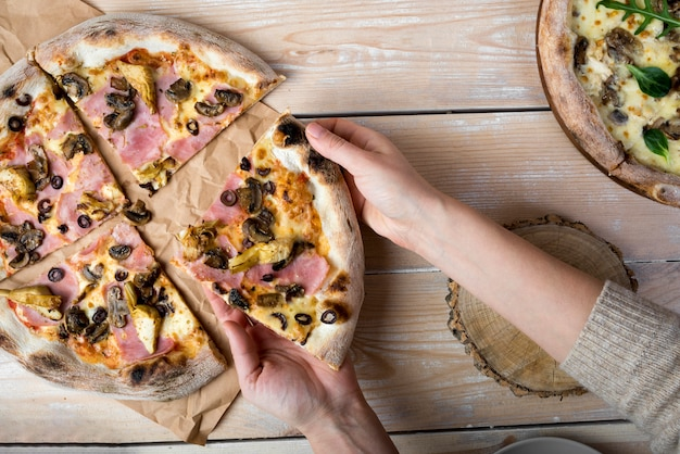 Elevated view of a human hand taking slice of pizza from brown paper over wooden table