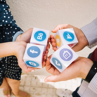 Elevated view of human hands holding blocks of mobile application icons