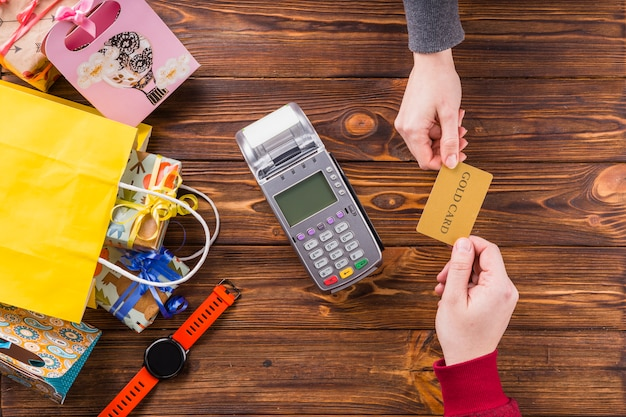 Elevated view of human hands holding gold card with swiping machine on wooden table