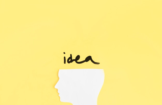 Elevated view of human head with idea word on yellow background