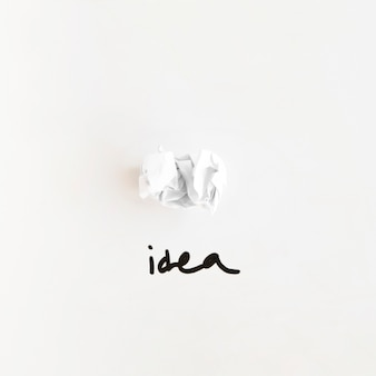 Elevated view of idea word near crumpled paper on white background